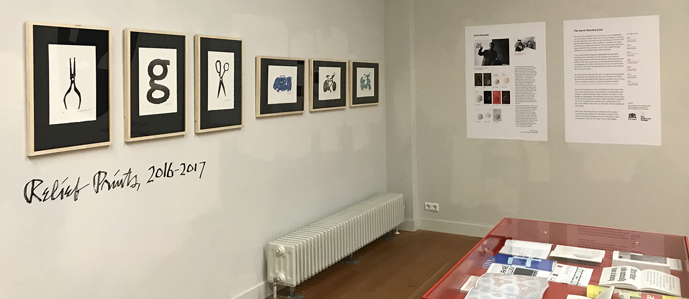 Photograph of framed relief prints by Cyrus Highsmith hanging on the exhibition wall.