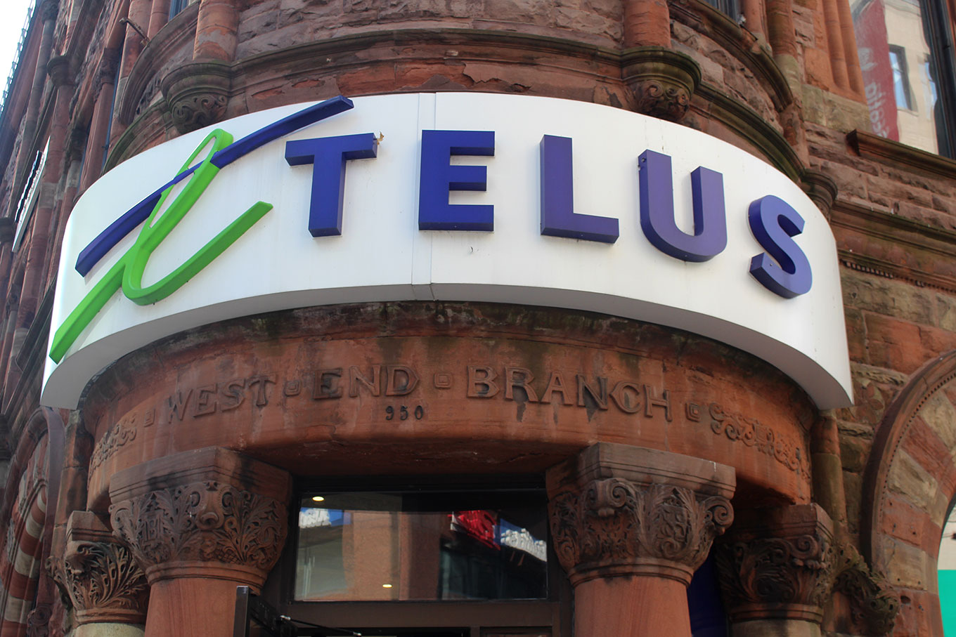 Laminated raparound Telus signage covers the original art-nouveau lettering above the door of what was formerly the Bank of Montreal.